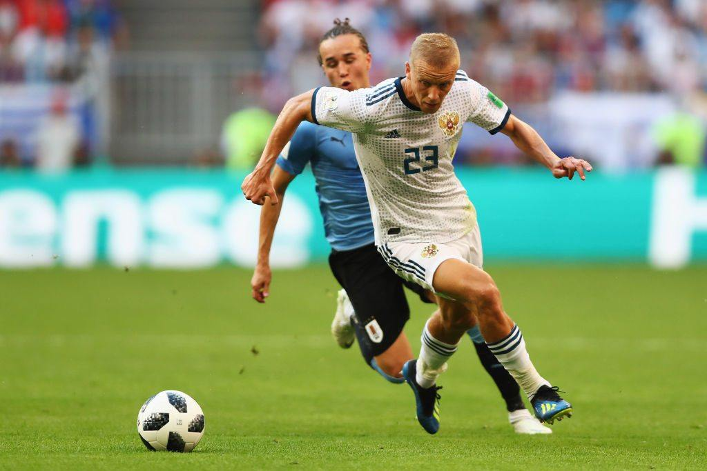 Diego Laxalt of Uruguay battles for the ball with Igor Smolnikov of Russia during the 2018 FIFA World Cup