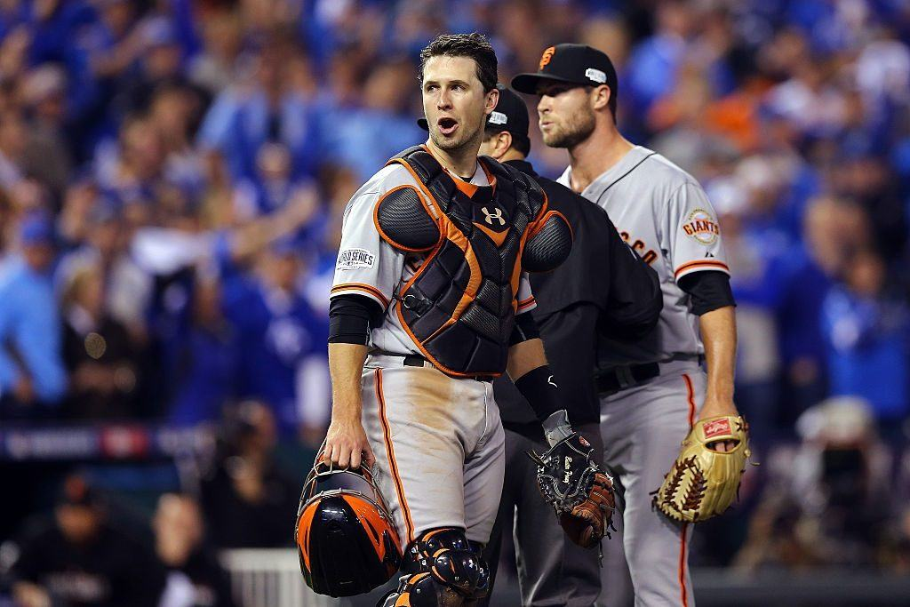 Buster Posey tries to keep Hunter Strickland from fighting with Salvador Perez of the Kansas City Royals