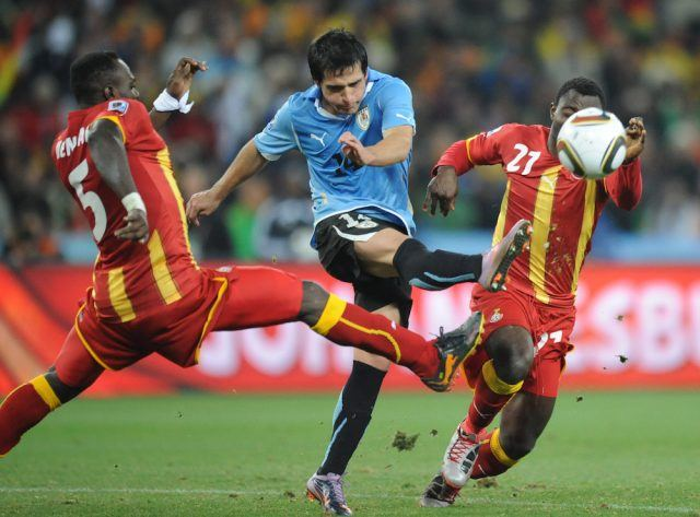 Uruguay's defender Maximiliano Pereira kicks the ball away from Ghana's defender John Mensah (L) and Ghana's midfielder Kwadwo Asamoah during the 2010 World Cup quarter-final match