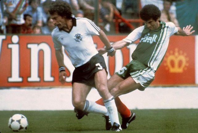 West German defender Paul Breitner (R) tries to control the ball under pressure from Algerian midfiedler Mustapha Dahleb duringthe 1982 World Cup