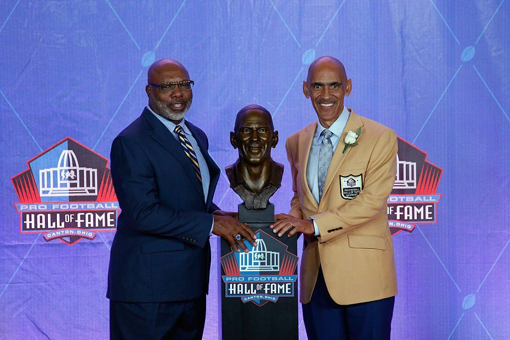 Tony Dungy (R), former NFL player and head coach, poses next to his bronze bust with friend and former NFL player, presenter Donnie Shell (L)