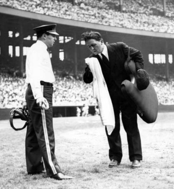 July 5, 1948-Suited up home plate ump Eddie Hurley does his best to stay cool on