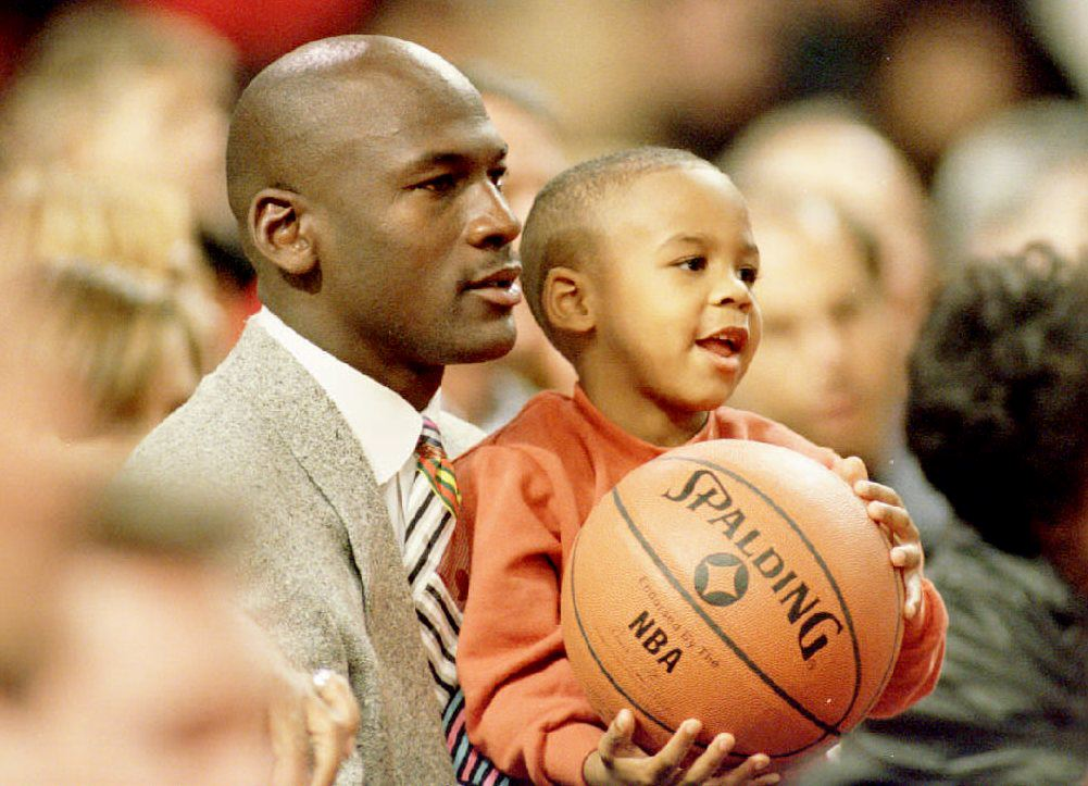 Michael Jordan holds Marcus Jordan