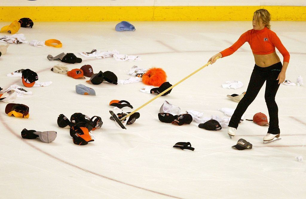 An ice crew member cleans the headgear off the ice
