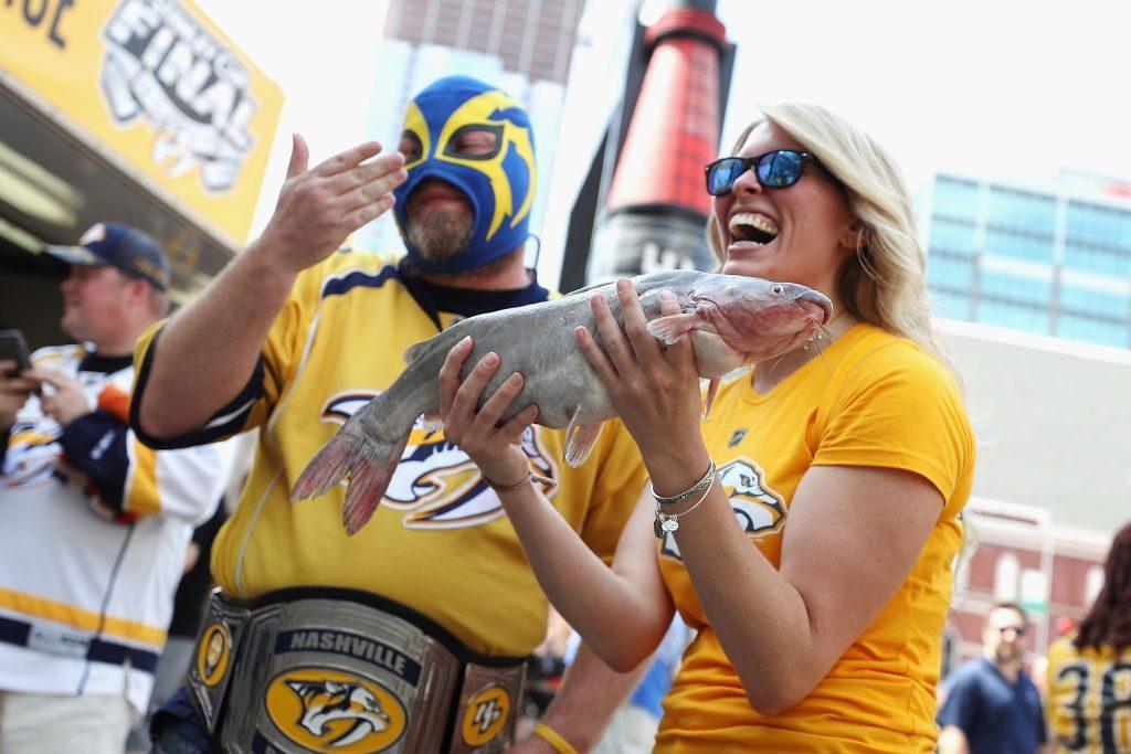 A Nashville Predators fan holds a catfish