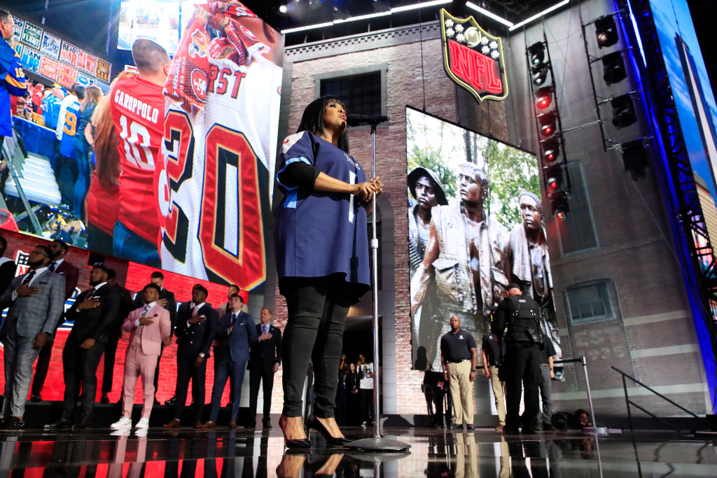 Players (background) stand for the national anthem before the first round of the 2019 NFL draft.