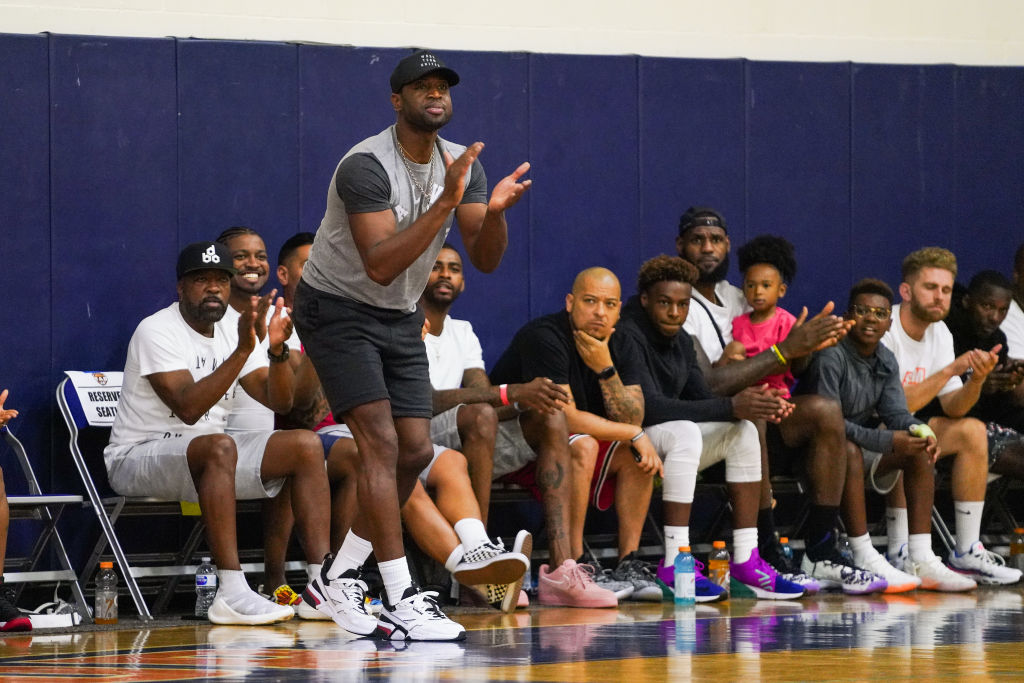 Former teammates Dwyane Wade (standing) and LeBron James (sixth from right with backwards hat) will be seeing a lot of each other when their sons play on the same high school basketball team.