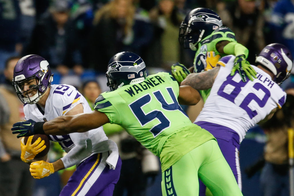 Bobby Wagner #54 of the Seattle Seahawks tackles Adam Thielen