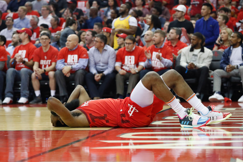 James Harden lays on the court after a hard foul