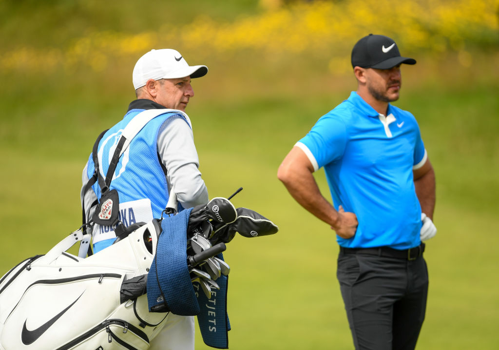 Brooks Koepka and Ricky Elliot look on
