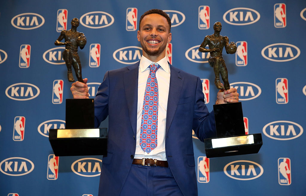 Stephen Curry of the Golden State Warriors poses with his back-to-back NBA Most Valuable Player Awards