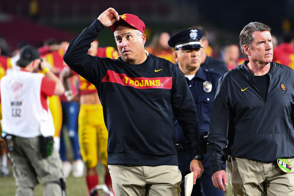 USC head honcho Clay Helton (center) is one of the college football coaches on the hot seat in 2019.