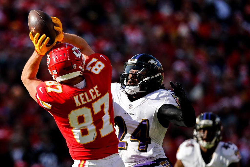 Travis Kelce #87 of the Kansas City Chiefs hauls in a pass over the coverage of Brandon Carr