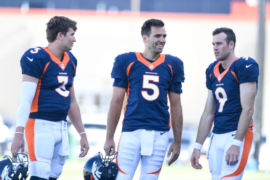 Joe Flacco (5) of the Denver Broncos jokes with Drew Lock (3) and Kevin Hogan (9) during Denver Broncos training camp