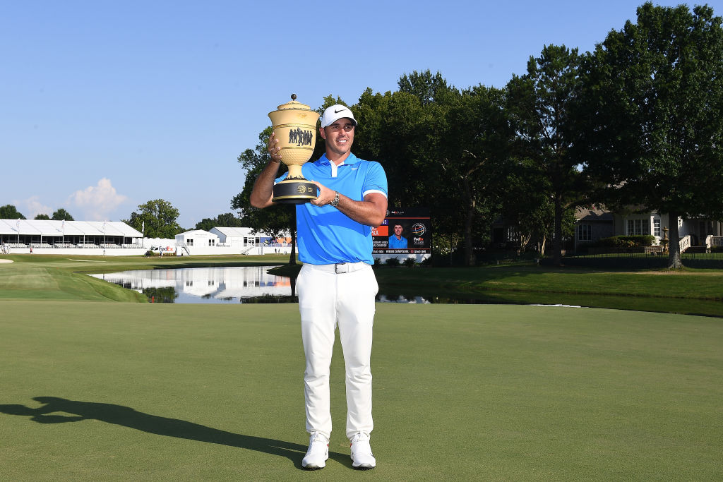 Brooks Koepka poses with the trophy