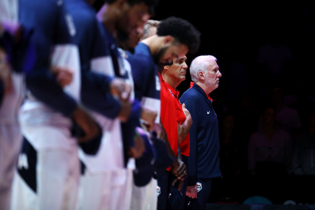 Gregg Popovich stands with Team USA during the national anthem