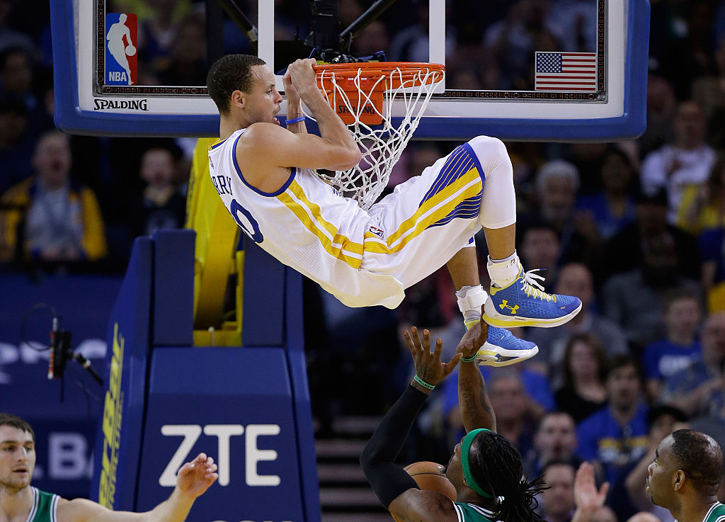 Golden State Warriors player Steph Curry hanging onto the rim after dunking