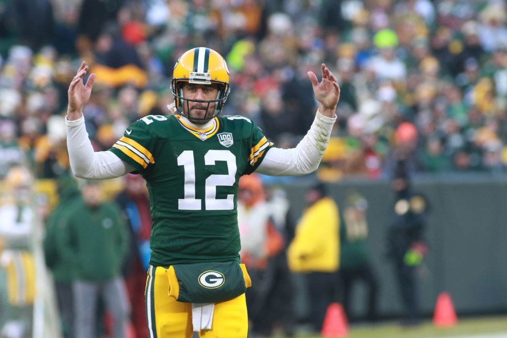 Aaron Rodgers lifts arms up on the field at Lambeau