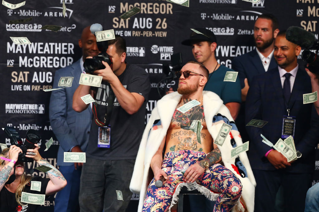 Conor McGregor at a press conference where money falls from the ceiling