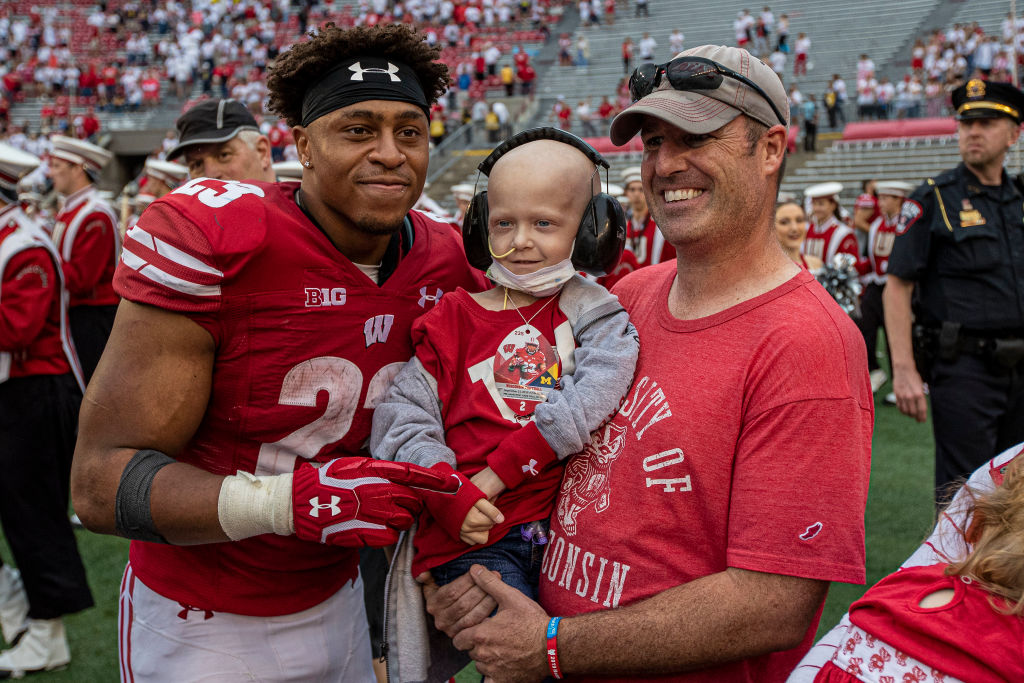 Jonathan Taylor poses with a fan after Wisconsin's 35-14 win over Michigan