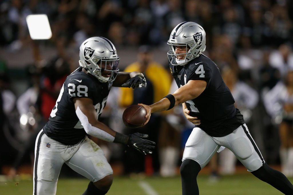 Quarterback Derek Carr #4 of the Oakland Raiders hands the ball off to running back Josh Jacobs #28