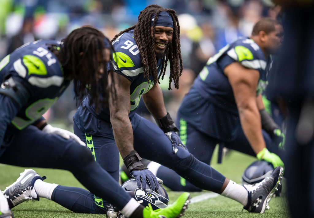 Jadeveon Clowney of the Seattle Seahawks and Ezekiel Ansah stretch before a game