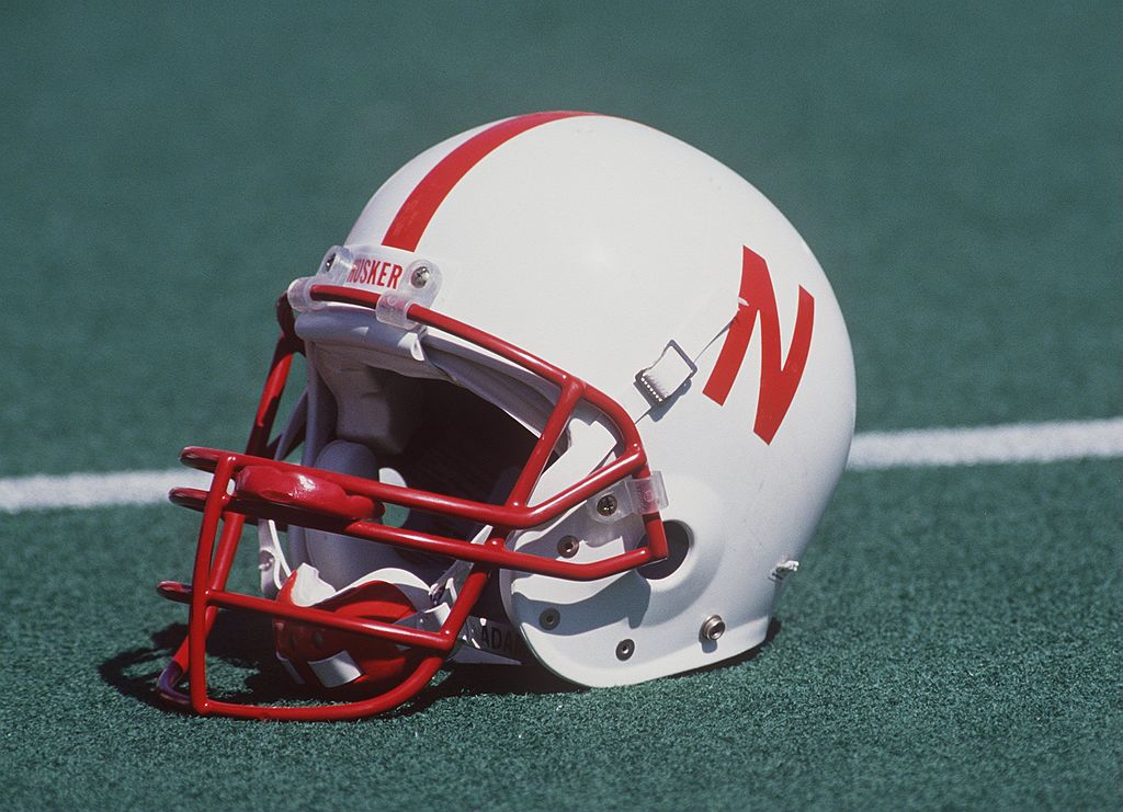 A Nebraska football helmet sitting on the field