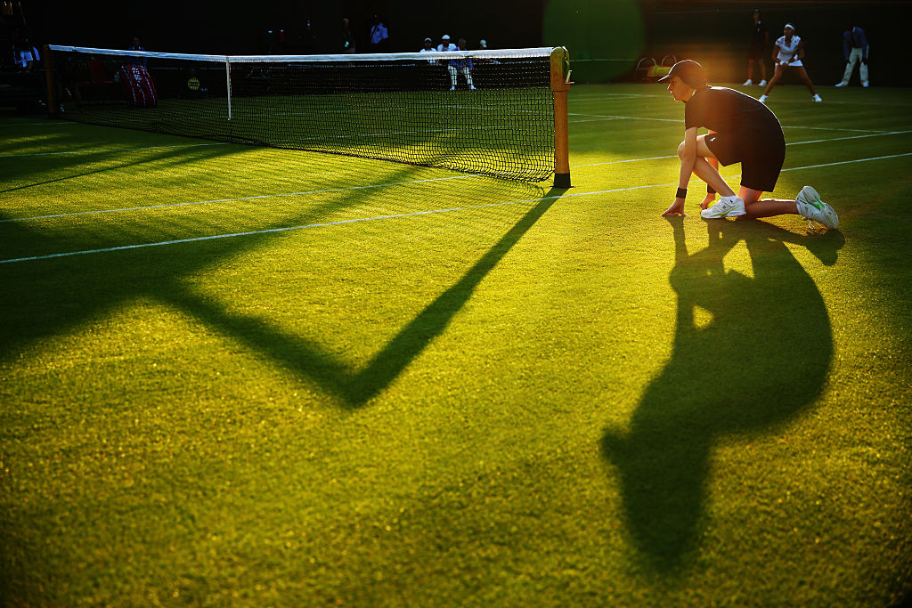 A tennis ball boy waiting on the sidelines at Wimbledon