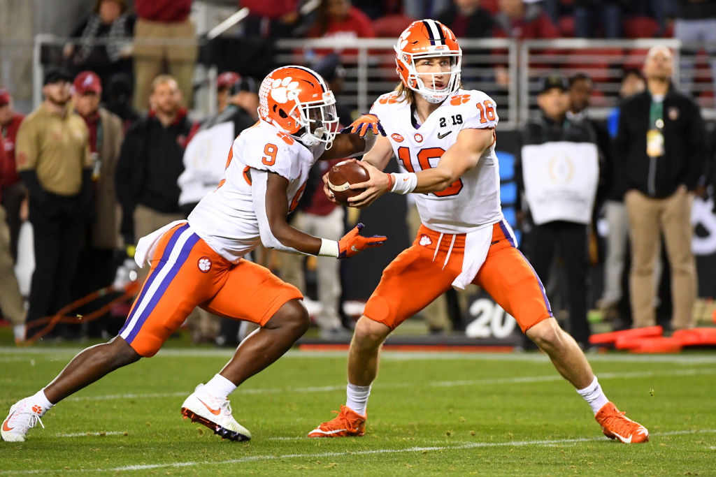 Clemson Tigers' quarterback Trevor Lawrence handing the ball to Travis Etienne