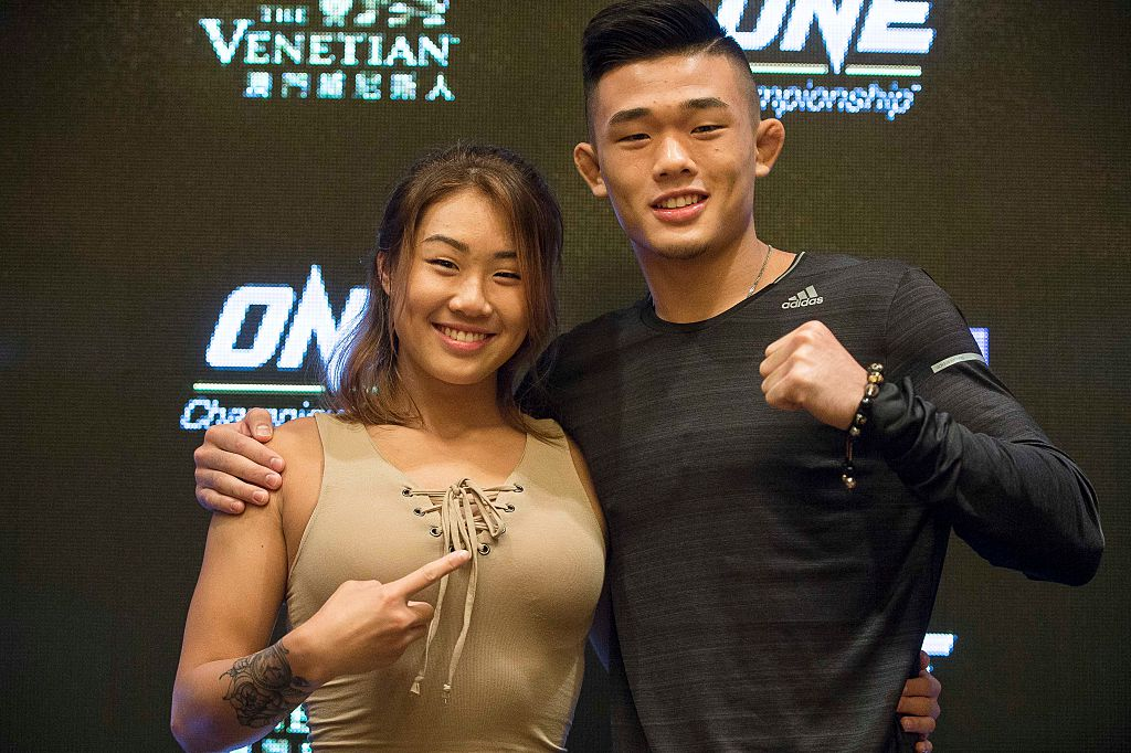 Asian MMA fighters Angela and Christian Lee posing for a photo