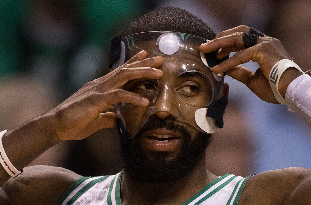 Boston Celtics' Kyrie Irving adjusts his face mask