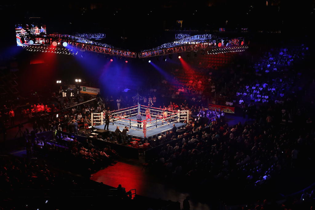 A packed arena with a boxing ring set up in the middle