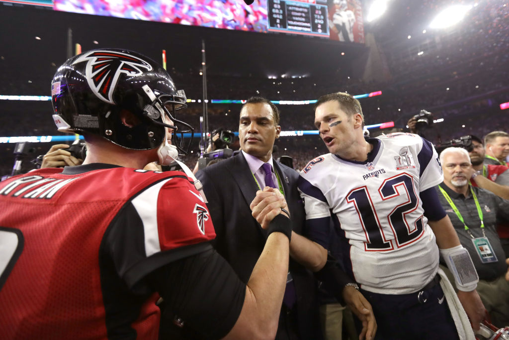 With Chad Steele in the background, Tom Brady of the New England Patriots speaks to Matt Ryan of the Atlanta Falcons after winning Super Bowl 51