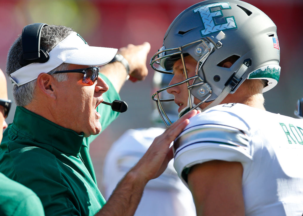 Eastern Michigan's coach Chris Creighton talking to his quarterback on the sideline.