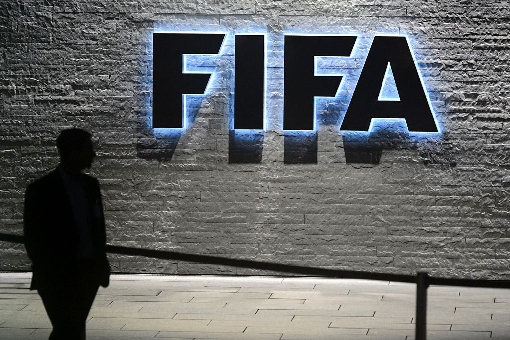 A man walks by a large FIFA sign on the wall.