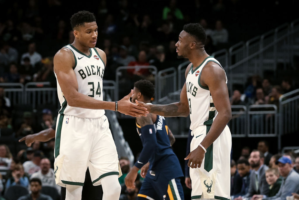 Giannis Antetokounmpo high fives a teammate during a Bucks game