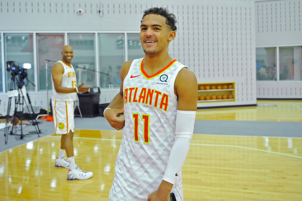 Atlanta Hawks guard Trae Young smiles as he walks toward reporters