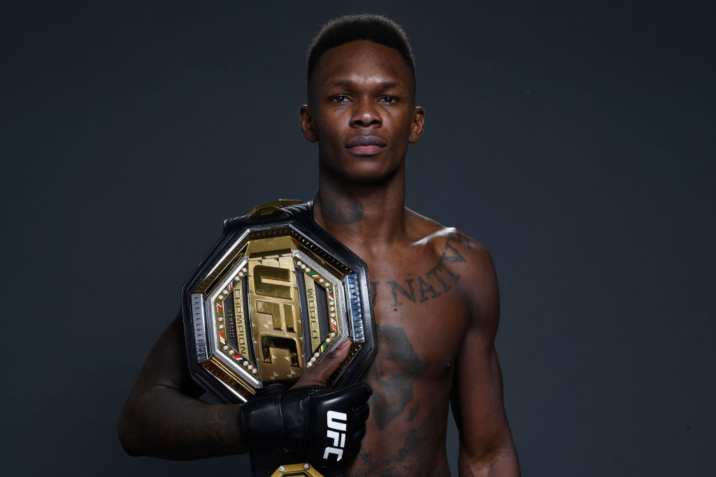 Nigerian UFC fighter Israel Adesanya holding his championship belt.