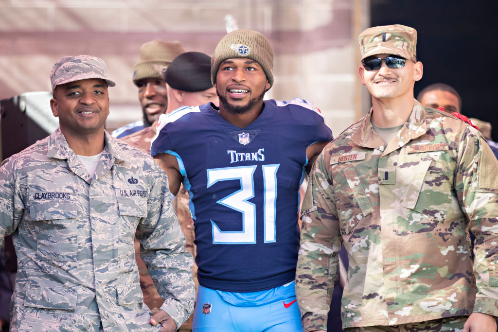 Kevin Byard poses for a photo with two men in military uniforms.