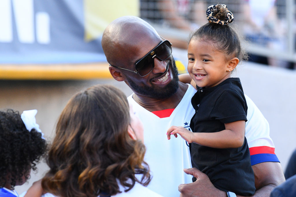 Kobe Bryant and his daughter Bianca look on during the USA Victory Tour match