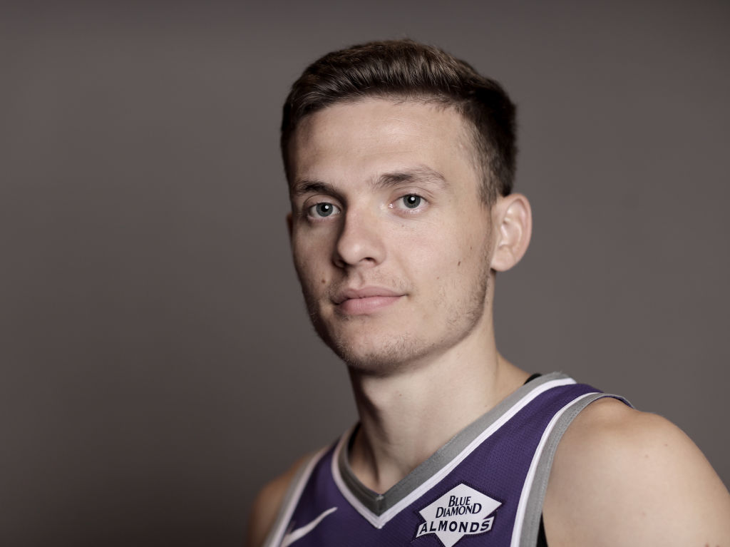 Kings' guard, Kyle Guy posing at a team photo shoot.