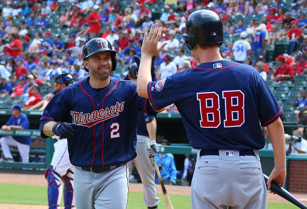 An MLB bat boy gives a player a high five after a home run.