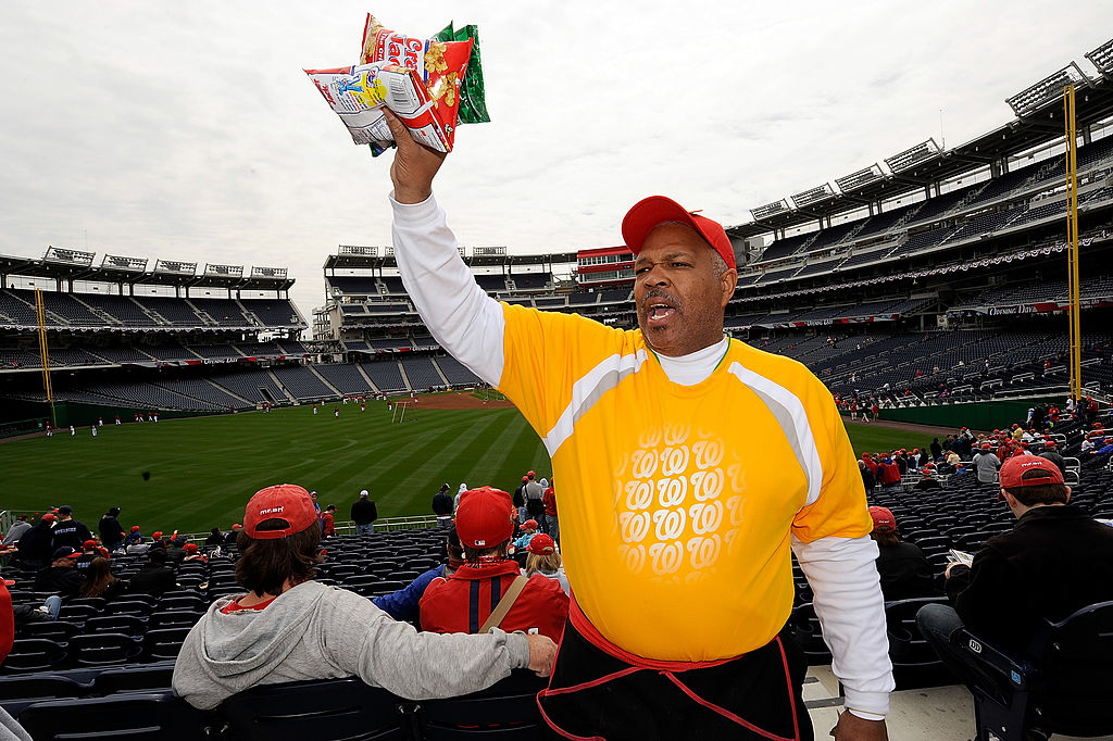 An MLB food vendor holds some bags of Cracker Jacks