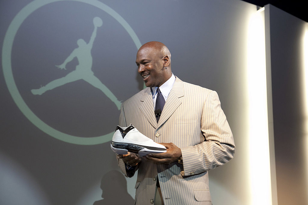Michael Jordan holding a shoe at a launch of a new sneaker.