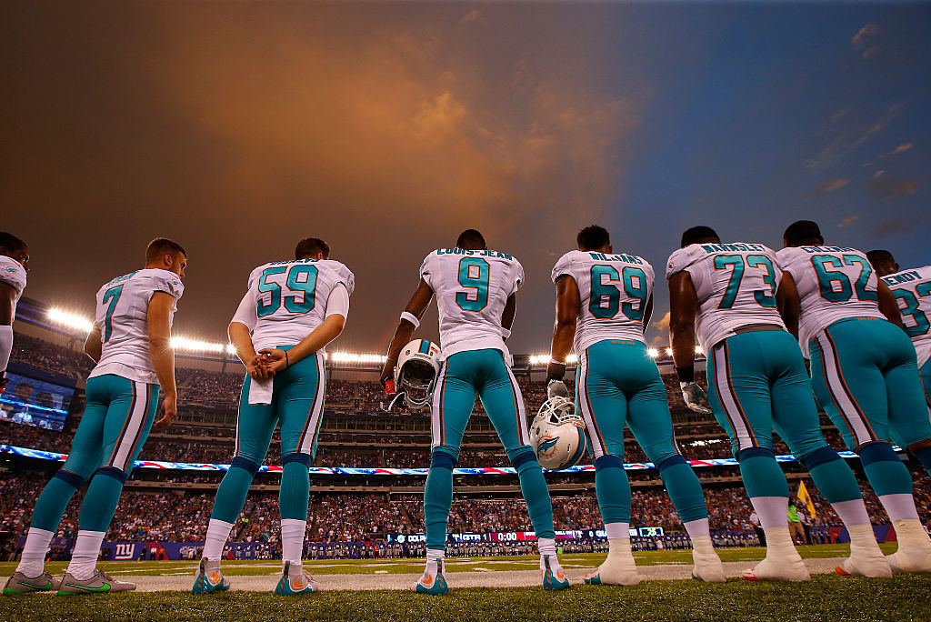 Miami Dolphins' players wearing their away jerseys on the sidelines.