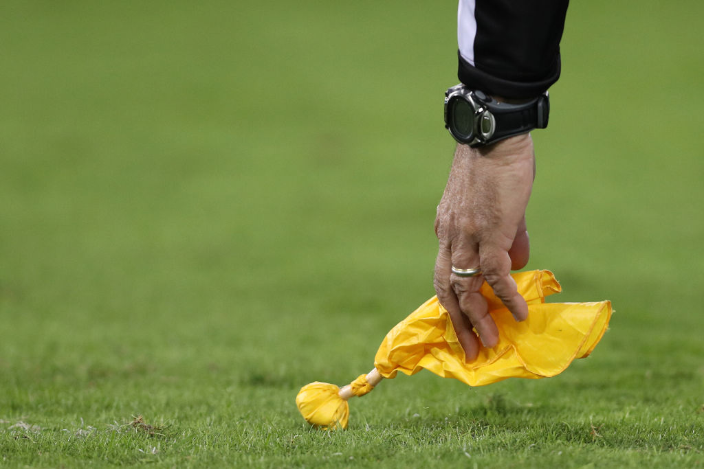 NFL referees signal penalties with a yellow flag.