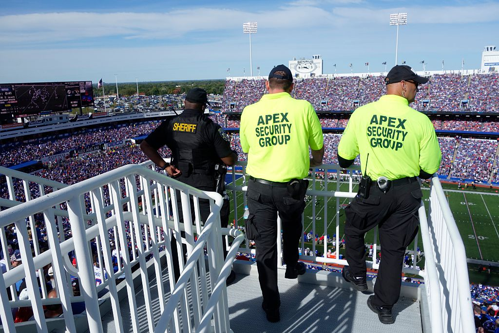 3 NFL security officials look out over a crowded stadium.