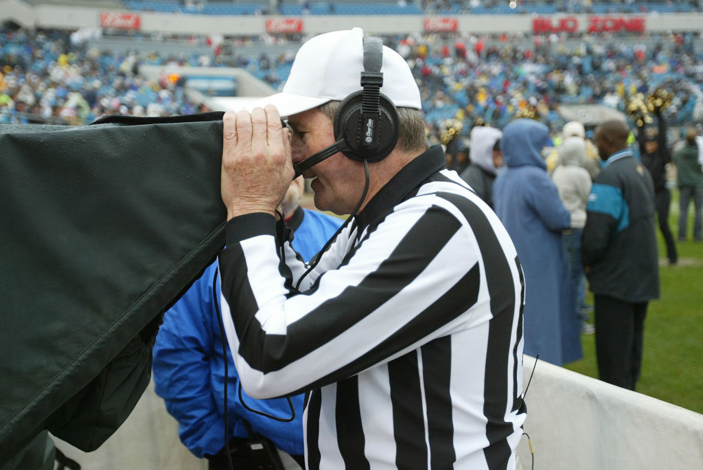 An NFL official goes to the booth for instant replay.