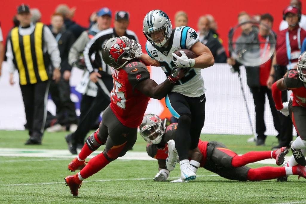 NFL running back Christian McCaffrey stiff arms a defender.
