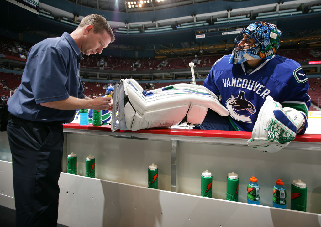 An NHL equipment manager sharpens the skates of a player.